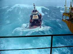 An oil platform receiving supplies in stormy weather